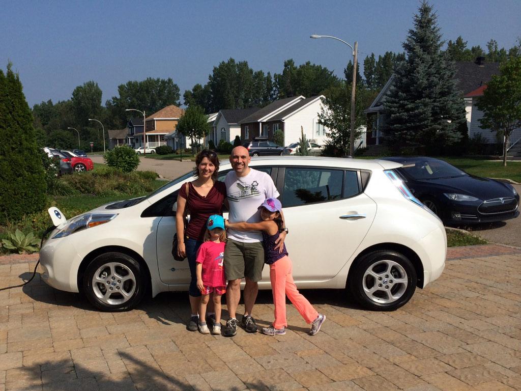 La famille devant la voiture électrique Nissan LEAF 2013 SV